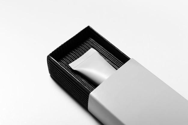 Close-up do tubo cosmético, embalagem em caixa preta na superfície branca