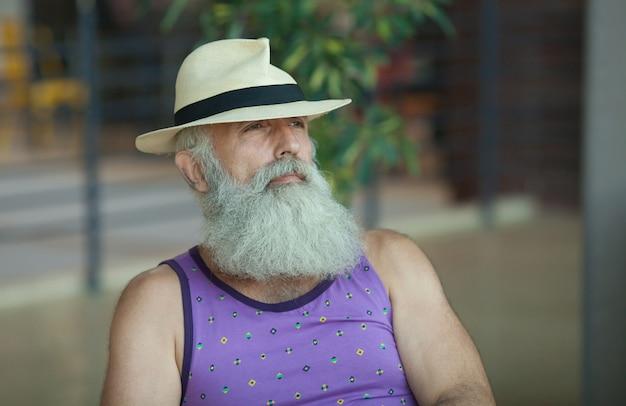 Close-up do velho hipster com barba e bigode, vestindo camisa roxa e chapéu de palha fedora.