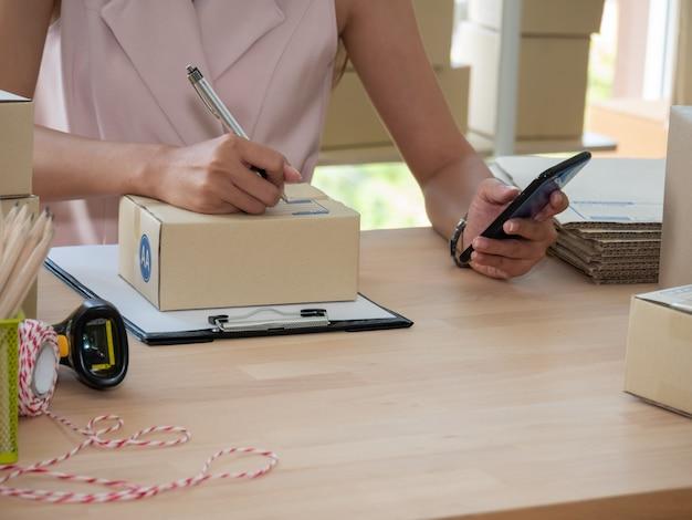 Close-up do vendedor de mão de mulher escrevendo o endereço na caixa de encomendas e verificar a ordem do produto no smartphone