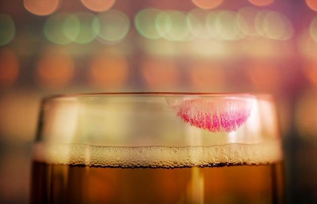 Close up do vidro da cerveja com marca vermelha do batom na barra ou no restaurante. humor feminino