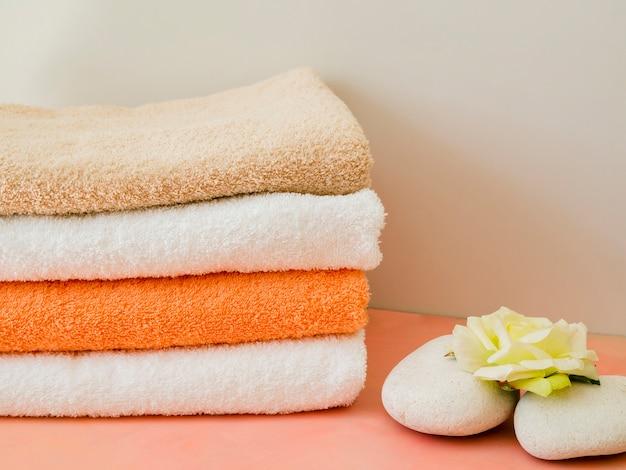 Close-up dobrado toalhas limpas com flor