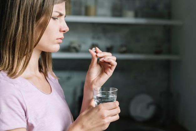 Close-up, doente, jovem, mulher, pílula, copo, água