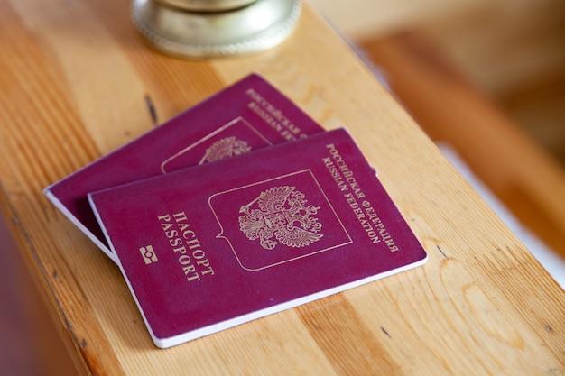 Close-up dois passaportes russos na mesa de recepção de madeira