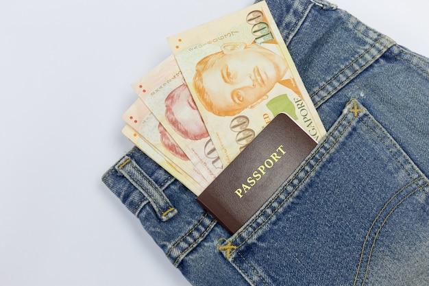 Close-up dólares de cingapura com passaporte no bolso da calça jeans