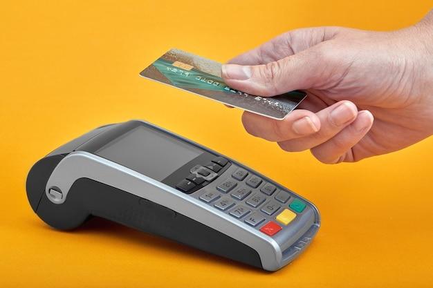 Close-up dos botões da máquina de pagamento com a mão humana segurando o cartão plástico por perto sobre fundo amarelo.
