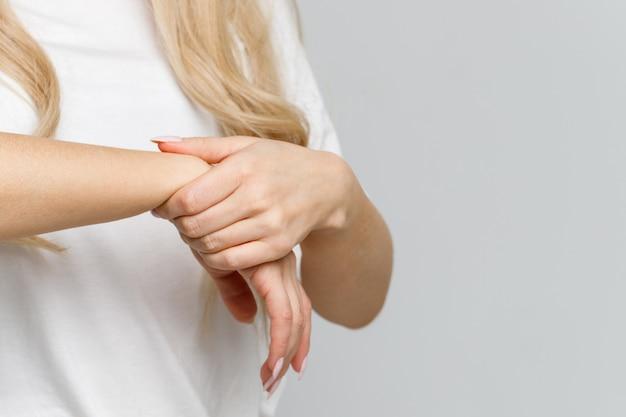 Close up dos braços da mulher que mantêm seu pulso doloroso causado pelo trabalho prolongado no computador, portátil. síndrome do túnel do carpo, artrite, doença neurológica