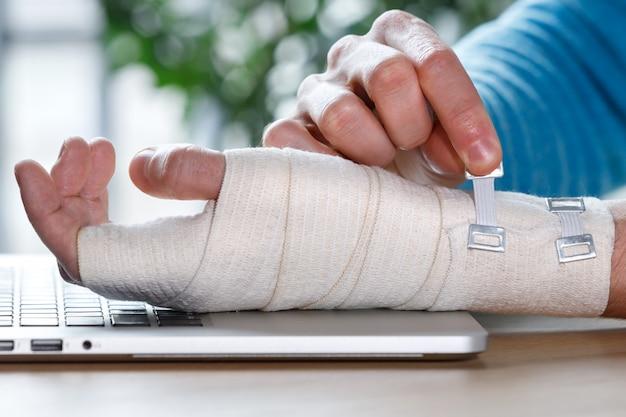 Close-up dos braços do homem envolvendo o pulso doloroso com bandagem ortopédica de suporte elástica flexível causada por trabalho prolongado no laptop
