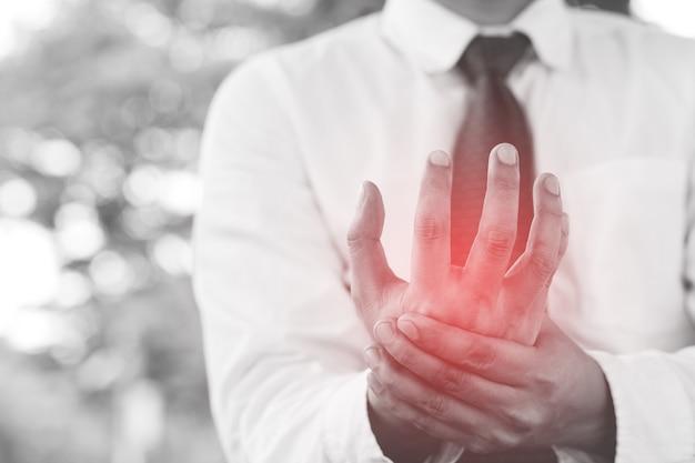 Close-up dos braços masculinos segurando seu pulso dolorido causado pela síndrome de escritório de trabalho prolongado.