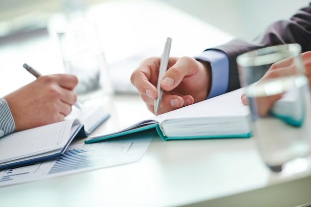Close-up dos homens de negócios que escrevem idéias