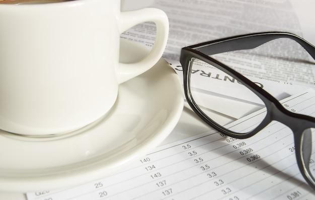 Close-up dos óculos elegantes dos homens negros e uma xícara de café branca em papéis comerciais.