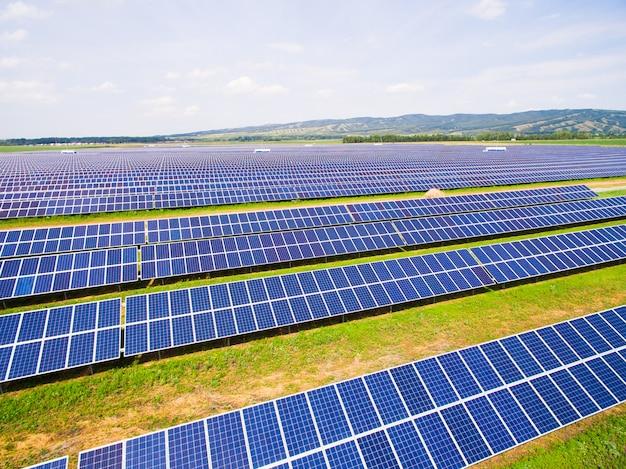 Close-up dos painéis solares na grama verde com céu azul.