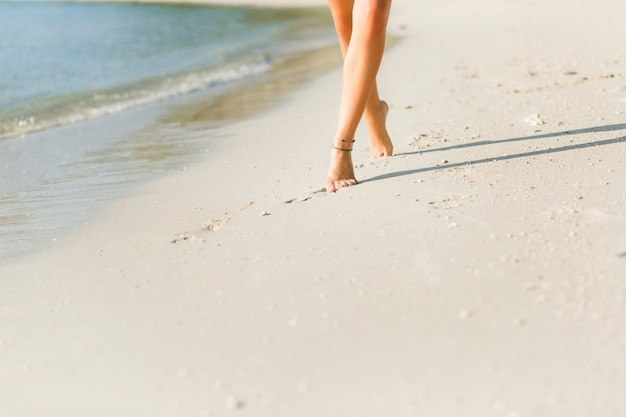 Close-up dos pés bronzeados de uma garota magra na areia. ela caminha perto da água. areia é ouro