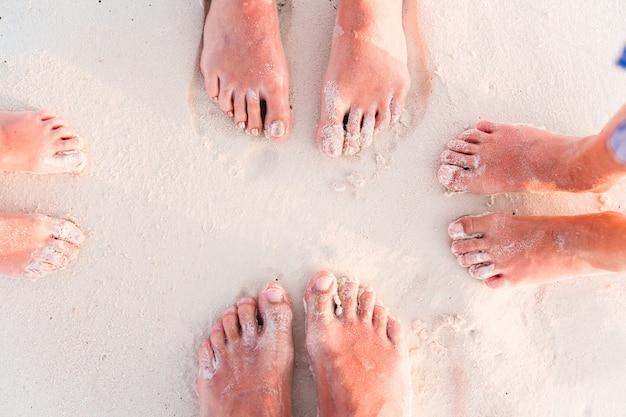 Close-up dos pés da família na praia de areia branca