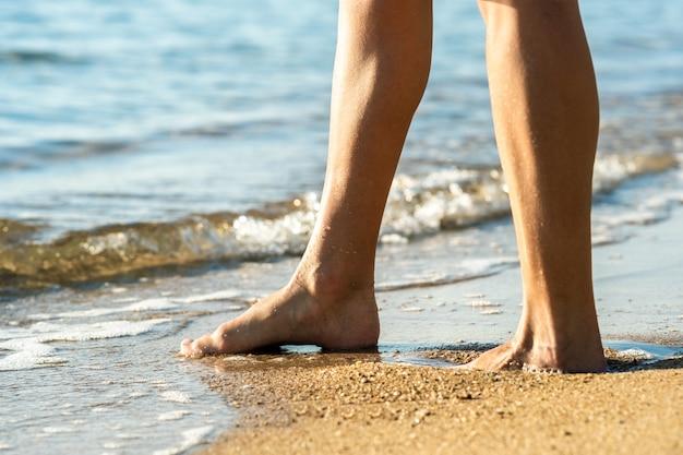 Close-up dos pés da mulher andando com os pés descalços na areia deixando pegadas na praia dourada