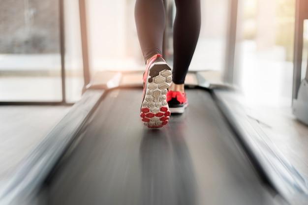 Close-up dos pés de pernas musculosas da mulher correndo no treino de esteira no ginásio de fitness