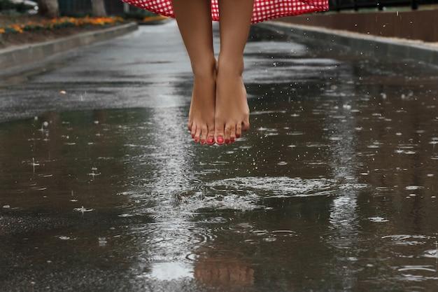 Close-up dos pés de uma menina dançando em uma poça após uma chuva de verão