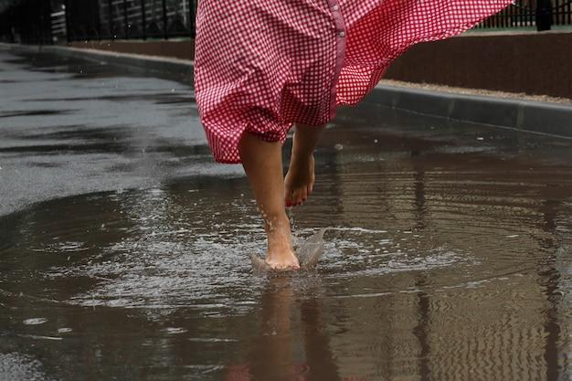 Close-up dos pés de uma menina que dançam em uma poça após uma chuva do verão.
