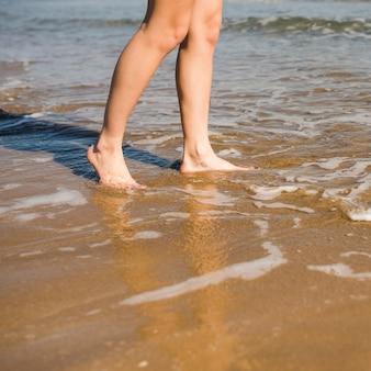 Close-up dos pés descalços da mulher na praia