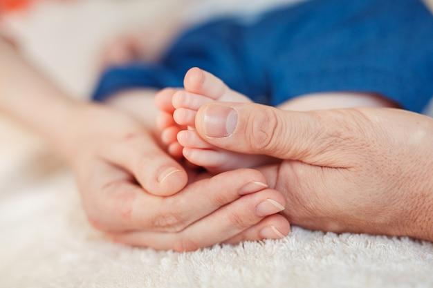 Close-up dos pés do bebê nas mãos da mãe