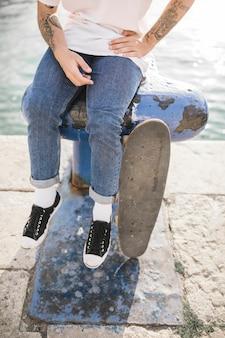 Close-up dos pés do homem com skate sentado no poste de amarração