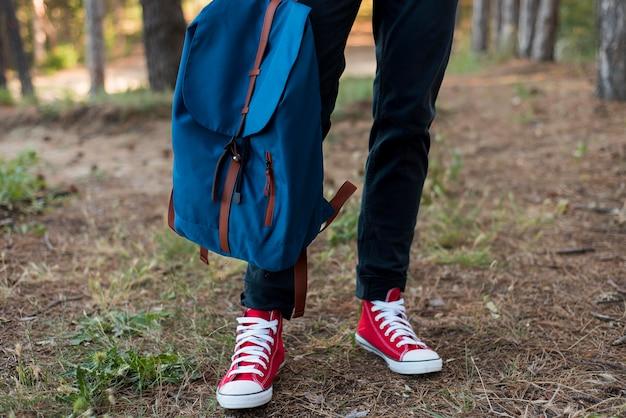 Close-up dos pés do homem e mochila na floresta