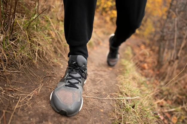 Close-up dos pés do homem na floresta