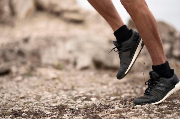 Close-up dos pés do homem na trilha na natureza
