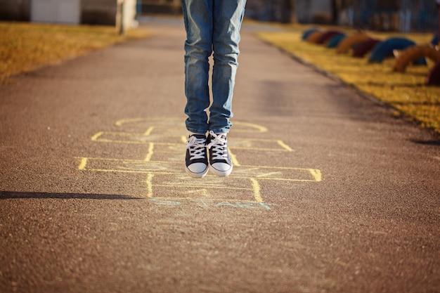 Close up dos pés do menino e jogo amarelinha no campo de jogos ao ar livre. jogo de rua popular amarelinha