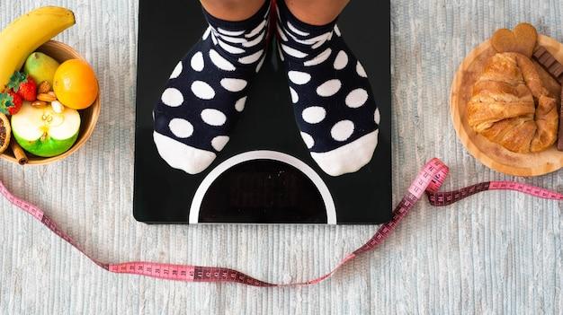 Close-up dos pés em uma balança para ver quanto é o peso dela e se ela emagreceu - estilo de vida saudável e escolha de conceito - escolhendo como comer