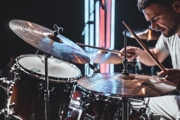Close-up dos pratos da bateria enquanto o baterista toca com uma bela iluminação em um fundo desfocado.