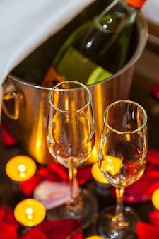 Close-up duas taças de champanhe, velas e pétalas de rosa