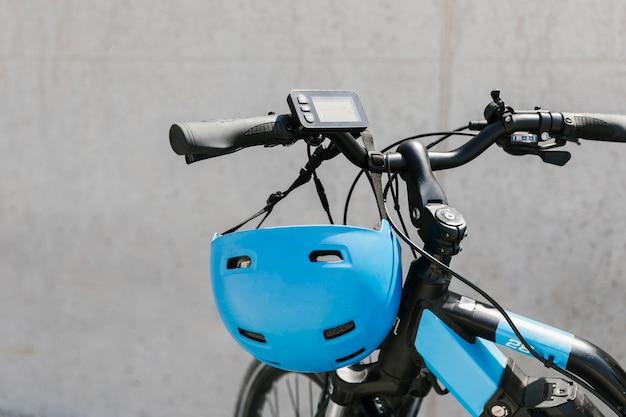 Close-up e-bicicleta com capacete no guidão