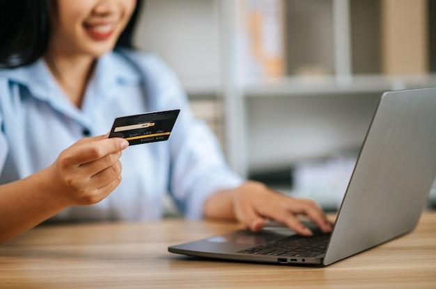 Close-up e cartão de crédito de foco seletivo nas mãos de uma mulher, ela segurando um cartão de crédito enquanto digita no laptop