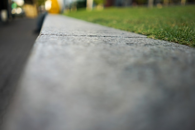 Close-up e macro passo de pedra plana ao lado do campo de grama para segundo plano.
