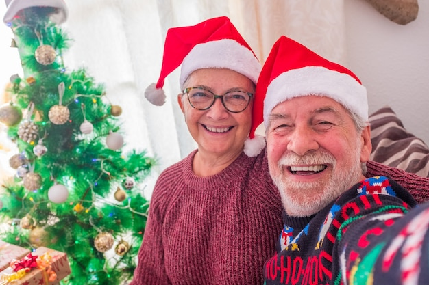 Close-up e o retrato de dois aposentados e idosos olhando para a câmera, sorrindo e tirando uma selfie no dia de natal em casa - pessoas maduras celebrando