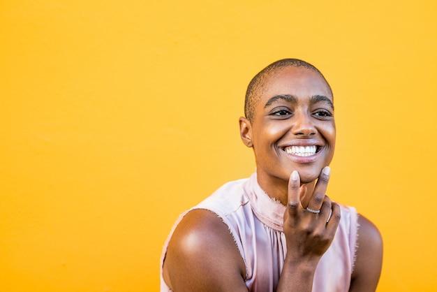 Close-up e o retrato de uma jovem e linda mulher afro-americana olhando para a câmera, sorrindo e abrindo os olhos - alegre menina bonita desfrutando