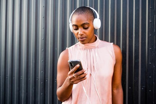 Close-up e o retrato de uma linda mulher negra e afro usando seu telefone enquanto ouve música com fones de ouvido brancos - parede preta ao fundo - amando a tecnologia