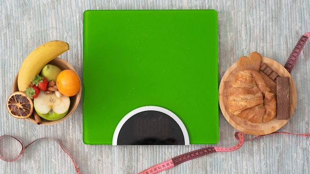 Close-up e retrato da balança no chão com frutas e alimentos saudáveis à esquerda e alimentos não saudáveis à direita