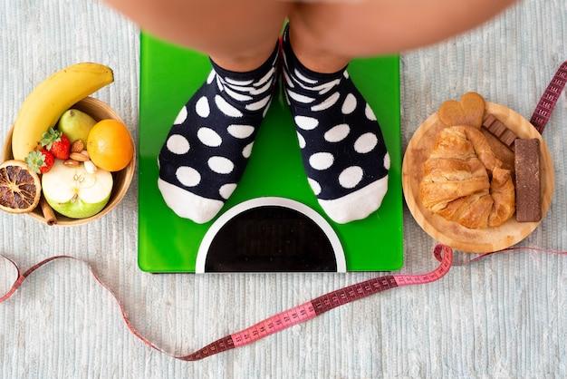 Close-up e retrato de pernas e pés pesando em uma balança para ver se ela perdeu peso após um estilo de vida saudável comendo frutas