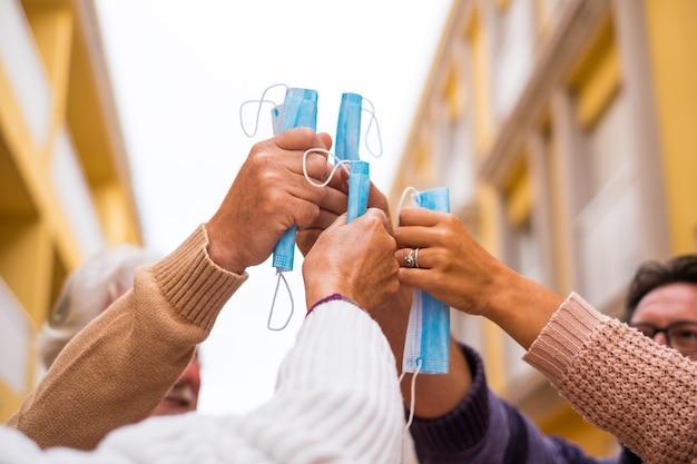 Close up e retrato de pessoas segurando suas máscaras médicas e cirúrgicas em suas mãos no centro da união - após covid-19 e conceito de liberdade de quarentena e estilo de vida
