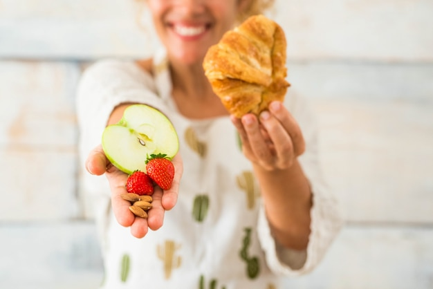 Close-up e retrato de uma linda mulher mostrando para a câmera alimentos saudáveis como frutas e por outro lado má alimentação como croissants
