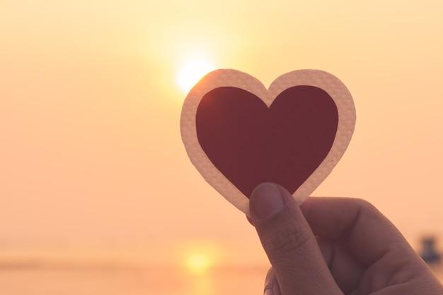 Close-up e silhueta de mão segurando coração vermelho durante o fundo por do sol