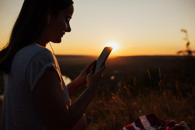 Close-up e vista lateral da mulher usando o telefone durante o pôr do sol lindo.