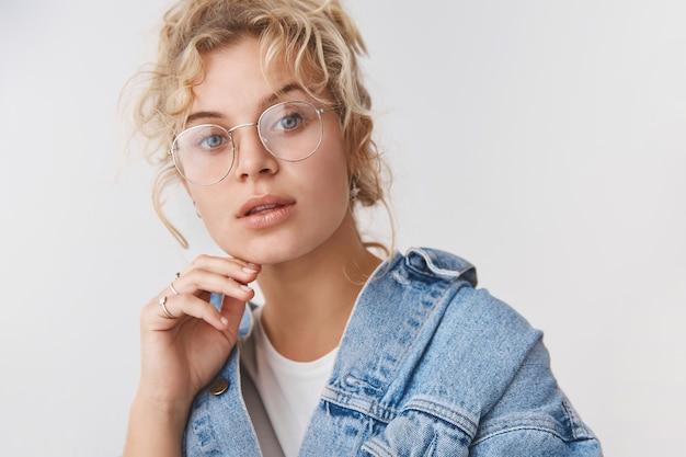 Close-up, elegante, bonita, elegante, loira, olhos azuis, blogueira, óculos transparentes, jaqueta jeans, tocando o queixo, câmera pensativa, intrigada, interessada, parede branca