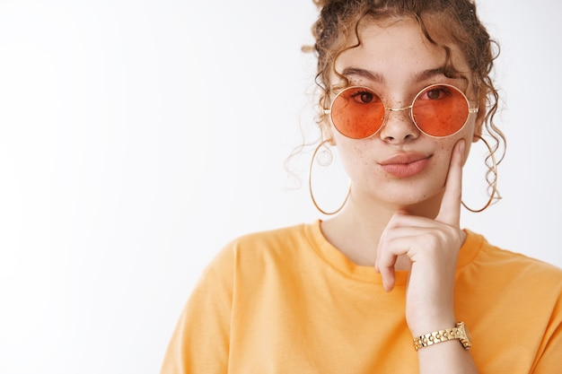 Close-up elegante glamour jovem ruiva aluna usar óculos de sol laranja t-shirt dobrar lábios pensativos ter desejo pensar tocar bochecha pensativo fazer suposição, pé fundo branco
