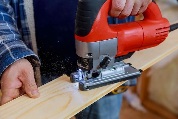 Close-up elétrico quebra-cabeça cortando um pedaço de madeira