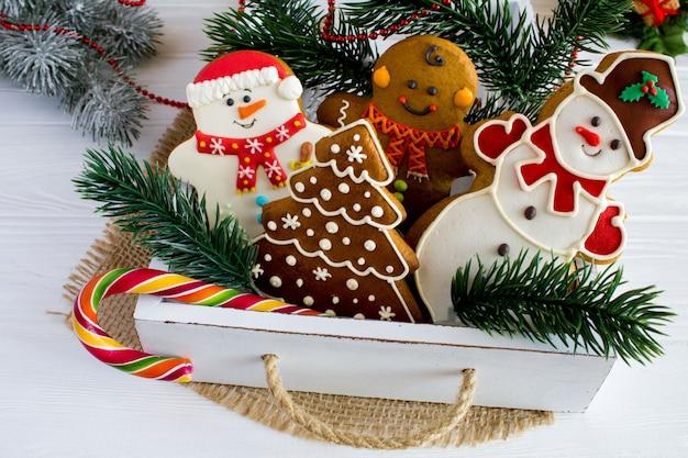 Close-up em biscoitos de natal em uma caixa com ramos de pinheiro