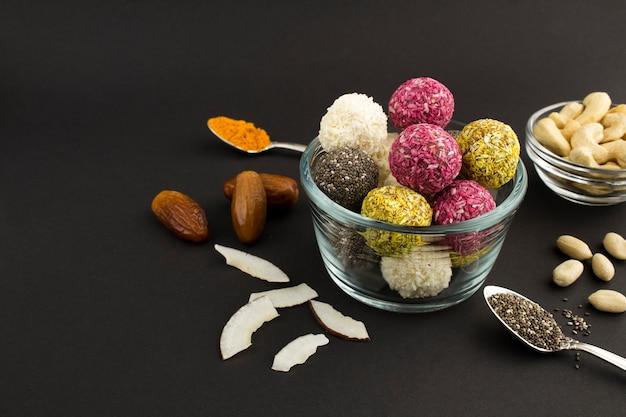 Close-up em bolas de energia diferentes na tigela de vidro e ingredientes no fundo preto. copie o espaço.