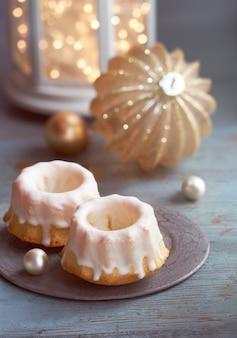 Close-up em bolos na mesa verde rústica com bugiganga dourada e luzes de natal na lanterna branca