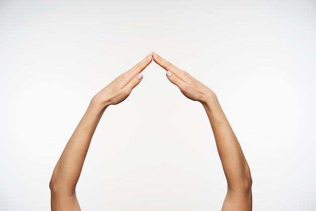 Close-up em braços bonitos imitando casa com as palmas das mãos dobradas